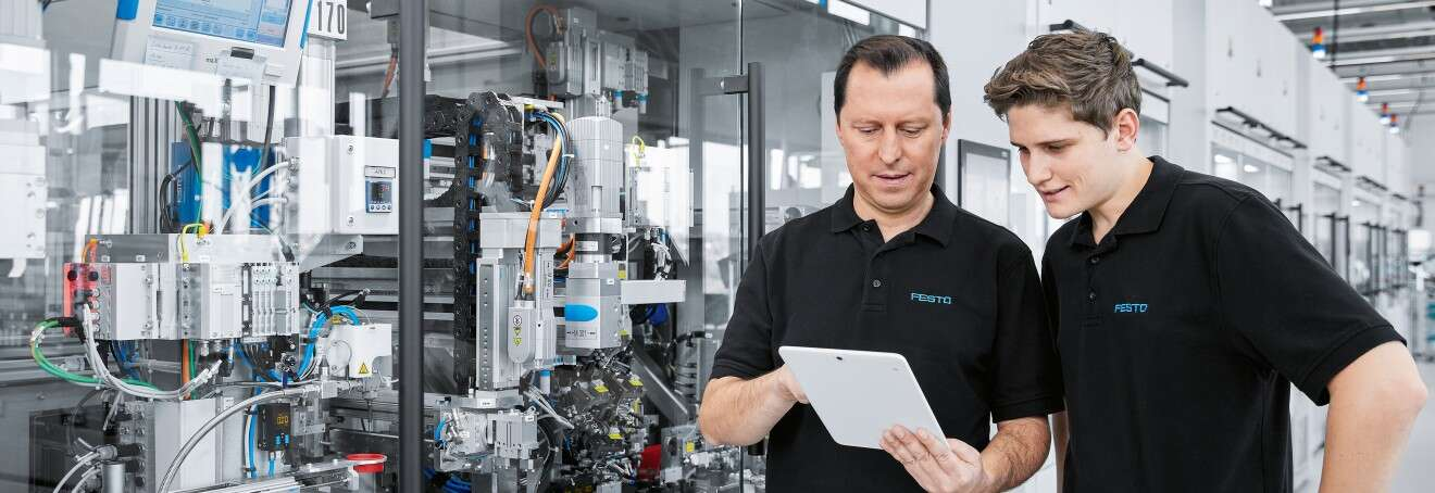 Digitalization of production: employee with tablet in production hall